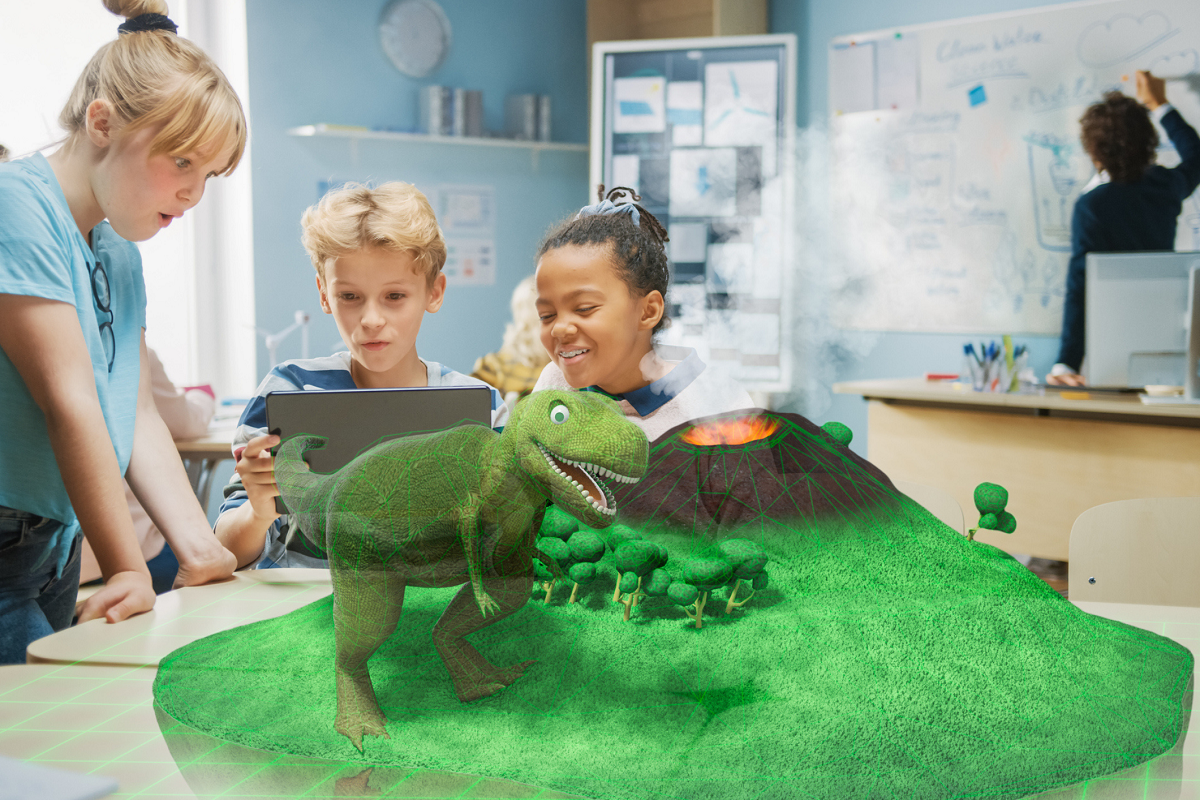 Three children in a classroom use a tablet with an augmented reality app.